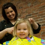 Child Receives a Haircut from Capri College Student